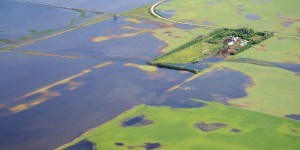 Floodwaters creep across fields toward a farmhouse south of Brandon, Man., in early July. Heavy summer rains in Saskatchewan and Manitoba led to unprecedented summer flooding in parts of the two provinces. ©DUC/Jeope Wolfe