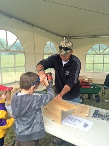 DUC's Danny Sears helps a young Duck Day attendee build a songbird nest box. ©DUC